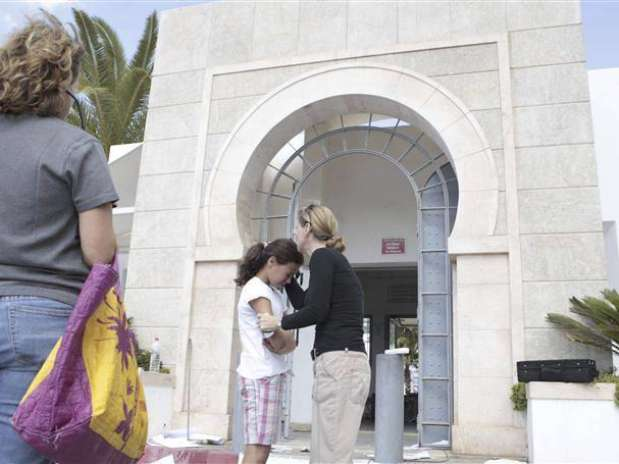 A teacher embraces a schoolgirl after witnessing the damage inside the American School after it was attacked by protesters in Tunis September 15, 2012.
