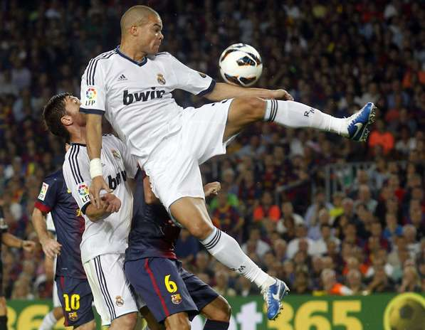 Real Madrid's Pepe (R) controls the ball over teammate Xabi Alonso (L) and Barcelona's Xavi Hernandez during their Spanish first division soccer match at Nou Camp stadium in Barcelona, October 7, 2012.    Photo: ALBERT GEA / REUTERS