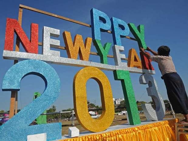 """Un trabajador alista el mensaje \""""Feliz Año Nuevo\"""" en Myanmar, país que por primera vez hará una cuenta regresiva pública para recibir al año 2013."""