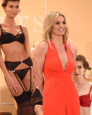 De macacão superdecotado, Britney desfila linha de lingerie