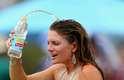 Com biquíni, fã de tenis joga água na cabeça. O dia foi tão quente em Melbourne que às 23h locais, no decorrer da rodada noturna de jogos, a temperatura estava na casa dos 35º C