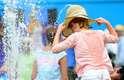 Criança se refresca do calor em fontana no Melbourne Park
