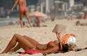 2 de abril Mulher lê um livro enquanto toma banho de sol na praia de Ipanema