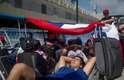 Jovem chileno descansa apoiado em malas no Sambódromo da Marquês de Sapucaí