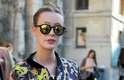 Óculos espelhados e mix de pulseiras complementam o look com jaqueta teddy de estampa floral
