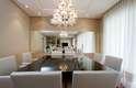 O espelho da sala de jantar reflete toda a mesa e a sala de estar. A proposta é da dupla Stela M. Sartori e Gabi Sartori. Informações: (11) 2592-7045/7071