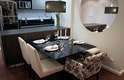 A mesa fica ao lado da bancada da cozinha e conta com três cadeiras e um banco. A proposta é da arquiteta Cinthia Garcia e da designer de interiores Andréia Karalkovas