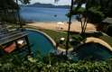 O desenho sinuoso da borda da piscina remete às ondas do mar, e o revestimento fulge usado na beirada imita a areia