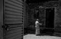 Mulher carrega panela com água para sua cada na favela de Alexandra, em Johannesburgo, na África do Sul. Água e o banheiro - porta do lado esquerdo - é dividido por cerca de 250 moradias.