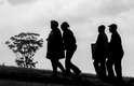 Moradores de Qunu sobem uma colina para acompanhar o enterro de Nelson Mandela num dos telões montados pelo governo