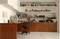 Nesse projeto de home office, os livros dividem as prateleiras com artigos decorativos...