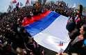"""Ativistas seguram uma enorme bandeira russa em frente ao prédio da administração regional em Donetsk, Ucrânia, neste domingo. Um grupo de pessoas invadiu o edifício do governo provincial: uma inscrição na bandeira russa colocada na fachada do local dizia: """"República Donetsk"""""""