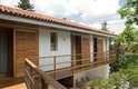 A varanda é, de certa forma, uma síntese do projeto: integra todos os quartos e capricha na madeira. As janelas dos quartos se transformaram em portas para aproveitar o terraço