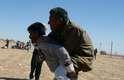 Um refugiado curdo sírio carrega nas costas um amigo que não suporta mais a caminhada