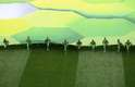 Colaboradores da Copa do Mundo estendem imagem no centro do campo na cerimônia de abertura