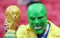 Torcedor brasileiro fantasiado de Máscara com a taça da Copa do Mundo em mãos na partida contra a Bélgica