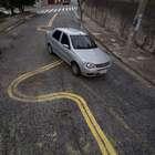 Moradores pintam faixas no asfalto para desviarem de buracos