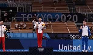 Eleftherios Petrounias, medalhista de bronze nas argolas, pede distanciamento para foto no pódio