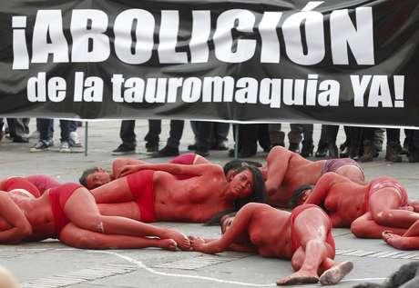 Jóvenes activistas yacen en el suelo con los cuerpos pintados de rojo simulando sangre en una protesta contra las corridas de toros en Bogotá, Colombia, el jueves 9 de febrero de 2012.
