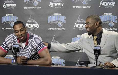 El pivote Dwight Howard recibe una palmada del gerente general del Magic, Otis Smith, durante una rueda de prensa el jueves 15 de marzo de 2012 en Orlando. Howard firmó el mismo jueves los documentos para dejar de lado la opción de terminar anticipadamente su contrato con el Magic, y seguir con el equipo al comenzar la temporada 2012-13.