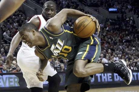 El escolta del Jazz de Utah, Alec Burks, derecha, pierde el equilibrio delante del escolta de los Trail Blazers de Portland, Raymond Felton, durante el primer cuarto del partido en Portland, Oregon, el lunes 2 de abril del 2012. El Jazz ganó por 102-97 a los Blazers.