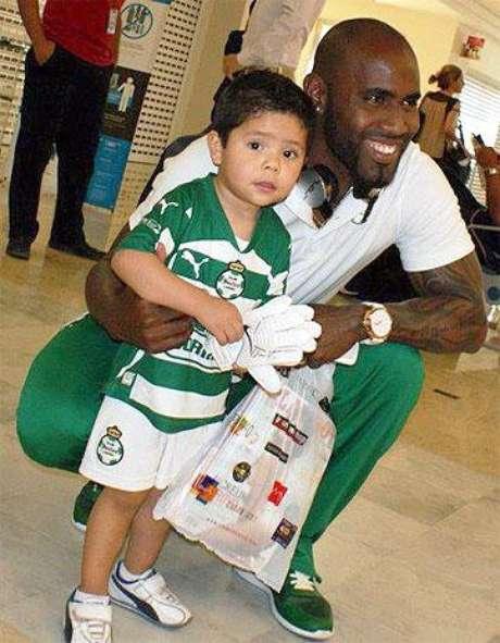 Felipe Baloy, defensa panameño de Santos Laguna, posa con un niño sosteniendo la revista de caballeros.