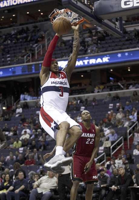 James Singleton (3), de los Wizards de Washington, hace una volcada en la segunda mitad del partido contra el Heat de Miami en Washington, el jueves 26 de abril de 2012. Los Wizards ganaron por 104-70 al Heat. Al fondo, james Jones (22), del Heat de Miami.  En la postemporada de la NBA que comienza el sábado, el Heat enfrentará a los Knicks de Nueva York.