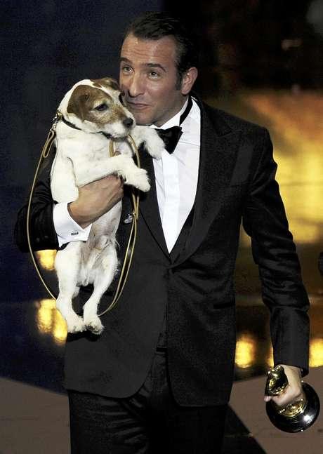 """ARCHIVO - En esta imagen del 26 de febrero de 2012, el actor Jean Dujardin sostiene a Uggie tras recibir el Oscar a la mejor película por """"The Artist"""" durante la 84ta edición de los Premios de la Academia en Hollywood. Uggie, el terrier de Jack Russell que participó en cintas como """"The Artist,"""" """"The Descendants"""" y """"Water for Elephants"""", contará con su propio libro biográfico, se anunció el viernes 27 de abril de 2012."""