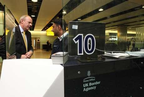 El ministro de Inmigración de Gran Bretaña, Damian Green, habla con un agente de aduanas Shafait Ali durante una visita a la Terminal 3 del Aeropuerto de Heathrow, en Londres, el martes 1 de mayo de 2012.