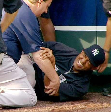 El panameño Mariano Rivera, de los Yanquis de Nueva York, al centro, hace gestos de dolor tras torcerse la rodilla izquierda mientras atrapaba bolas durante una práctica de bateo antes del partido de visita contra los Reales de Kansas City, el jueves 3 de mayo de 2012.