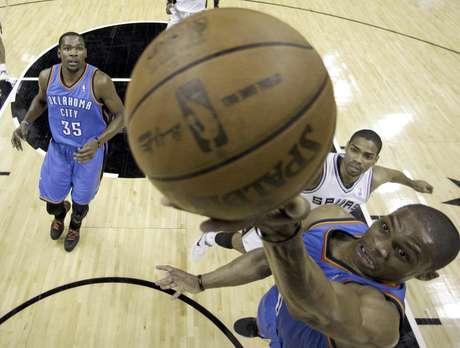 Russell Westbrook, del Thunder de Oklahoma City, encesta ante la mirada de su compañero Kevin Durant (35) y el jugador de los Spurs de San Antonio Gary Neal (14) durante la primera mitad del Juego 5 de la serie por el campeonato de la Conferencia del Oeste de la NBA el lunes 4 de junio de 2012, en San Antonio. El Thunder venció 108-103 a los Spurs para tomar una ventaja de 3-2 en la serie.