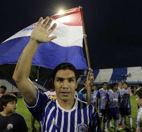 El delantero Salvador Cabañas saluda frente a una bandera paraguaya durante un encuentro entre 12 de octubre y Martín Ledesma por la tercera división del fútbol paraguayo en Itauguá, abr 14 2012. El entrenador del club paraguayo en el que juega Salvador Cabañas -quien volvió al fútbol luego de recibir un disparo en la cabeza- renunció el miércoles, por lo que consideró presiones para incluir entre los titulares del equipo al delantero.
