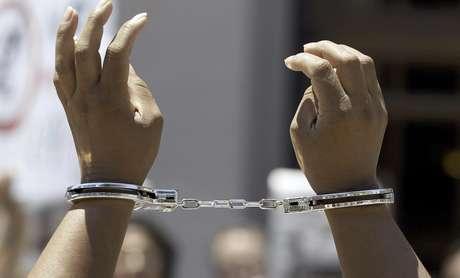 Juana Villegas protesta con esposas en las manos durante una movilización afuera de la Corte Suprema de Tenesí, en Nashville, el jueves 14 de junio de 2012. En 2008, Villegas estuvo encarcelada. El abogado de un grupo de inconformes expuso los argumentos por los cuales demandan a la corte que impida a la oficina del alguacil del condado de Davidson participar en un programa federal que permite a los agentes de esa dependencia ejecutar algunas funciones de agentes de inmigración.