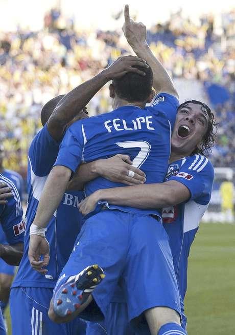 Felipe Martins, del Impact de Montreal es alzado en brazos por su compañero Zarek Valentin, después de anotar frente a los Sounders de Seattle en el partido del sábado 16 de junio de 2012