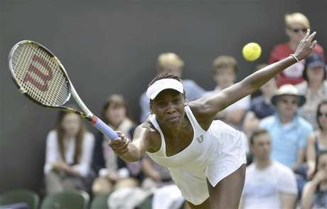 Venus Williams of the U.S. hits a return to Elena Vesnina of Russia during their women's singles tennis match at the Wimbledon tennis championships in London June 25, 2012.