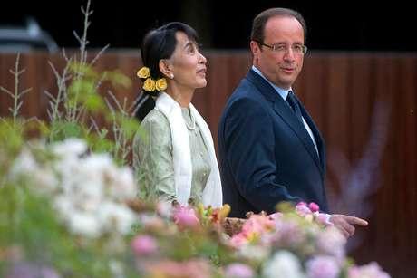 ARCHIVO - En esta foto del 26 de junio del 2012, la líder opositora de Mianmar Aung San Suu Kyi y el presidente francés Francois Hollande caminan por el Palacio del Elíseo en París. Multitudes jubilosas recibieron el sábado a Suu Kyi en Mianmar a su regreso de su gira por Europa, donde ganó un apoyo entusiasta para su papel en la transición democrática en su país y fue celebrada como una jefa de estado.