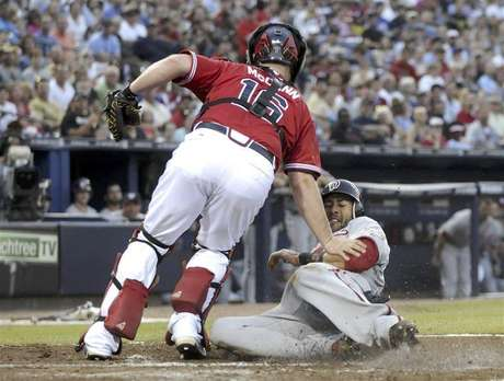 Washington Nationals runner Michael Morse slides in safe past Atlanta Braves catcher Brian McCann in the third inning at their MLB National League baseball game at Turner Field in Atlanta, Georgia June 29, 2012.