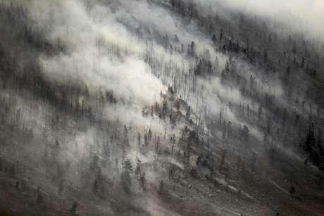 Un súbito cambio en la dirección de viento empuja el humo hacia la cima de Sheep Mountain mientras se extiende el incendio de Squirrel Creek, el martes 3 de julio de 2012, cerca de  Woods Landing, Wyoming.