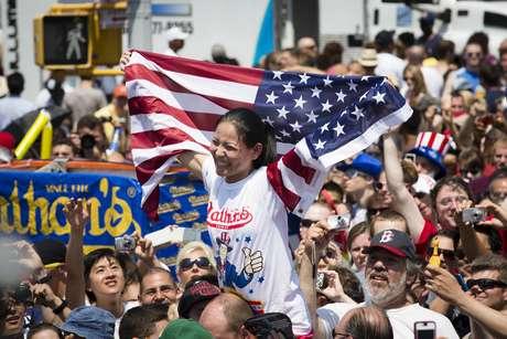 """Sonya """"La viuda negra"""" Thomas es cargada mientras celebra el título de campeona comedora de hot dogs, en el concurso anual de Coney Island, Nueva York, el miércoles 4 de julio de 2012. (Foto AP/John Minchillo)"""