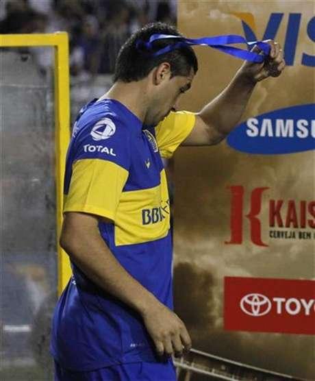 El jugador Juan Román Riquelme, del club argentino Boca Juniors, remueve su medalla luego de la derrota de su equipo frente al brasileño Corinthians en la final de la Copa Libertadores de América disputada en Sao Paulo, julio 4 2012.