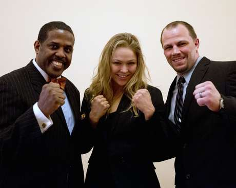 Sen. Kevin Parker, D-Brooklyn, left, poses with mixed martial arts athletes Ronda Rousey, center, and Nick Catone at the Capitol in Albany, N.Y., on Wednesday, April 18, 2012.