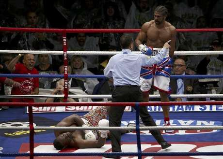 Britain's David Haye (R) looks down at opponent Dereck Chisora after scoring a fifth round knockout in their fight for the vacant WBO and WBA International Heavyweight Championship at Upton Park in London July 14, 2012.