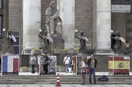La gente camina entre sirenas, el símbolo de la ciudad de Varsovia, decoradas con las banderas de los países que fueron representados en la Euro 2012 en Varsovia, Polonia, el viernes 13 de julio de 2012. La UEFA obtendría ganancias ligeramente menores por la Euro 2012, en comparación con el campeonato de hace cuatro años.
