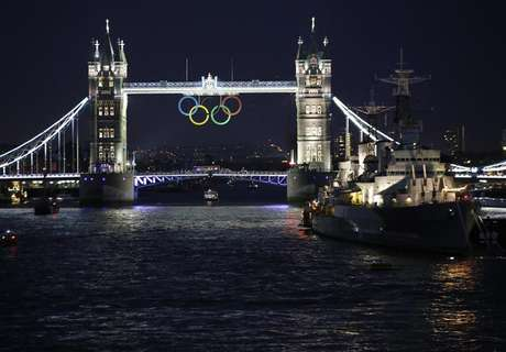 The Olympic rings are illuminated while suspended from Tower Bridge, near the HMS Belfast museum warship, as organisers marked one month to go until the London 2012 Olympic Games in London June 27, 2012.