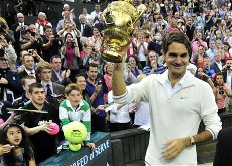 Roger Federer of Switzerland holds the winners trophy after defeating Andy Murray of Britain in their men's singles final tennis match at the Wimbledon Tennis Championships in London July 8, 2012.