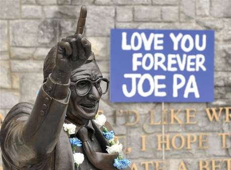 Signs and flowers are seen at the statue of the late Penn State football coach Joe Paterno, before the annual Spring football scrimmage in State College, Pennsylvania April 21, 2012.