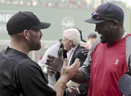 El tercera base de los Medias Blancas de Chicago Kevin Youkilis, izquierda, saluda a su ex compañero de equipo David Ortiz, bateador designado de los Medias Rojas de Boston, durante la práctica de bateo previa a su juego en el Fenway Park, el lunes 16 de juliuo de 2012, en Boston.