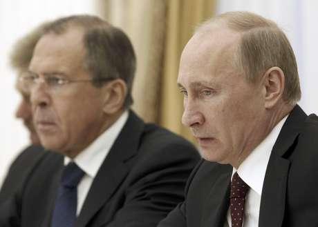 El presidente de Rusia Vladimir Putin, derecha, y el ministro de relaciones exteriores Sergey Lavrov participan en una reunión con el primer ministro de Turquía en el Kremlin en Moscú el miércoles 18 de julio del 2012. Rusia se opone enérgicamente a las sanciones al gobierno del presidente Bashar Assad si no retira sus tropas y armamento pesado de las áreas pobladas de Siria dentro de 10 días, tal como estipula una resolución que será sometida a votación en la ONU el jueves 19 de julio del 2012.