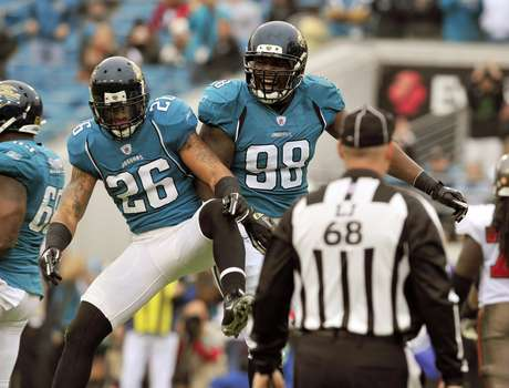 Former Jacksonville Jaguars defensive tackle Nate Collins (98) celebrates his fumble recovery for a touchdown with free safety Dawan Landry (26) during the first half of an NFL football game against the Tampa Bay Buccaneers on Sunday, Dec. 11, 2011, in Jacksonville, Fla.