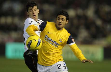 Valencia's defender Angel Dealbert (L) vies for the ball with Real Sociedad's Mexican forward Carlos Vela during the Spanish league football match Valencia CF vs Real Sociedad on January 14, 2012 at the Mestalla stadium in Valencia. Real Sociedad won 1-0.